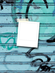 Blank square photo frame with adhesive tape on aqua metal shutter with graffiti spray paint