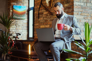 Urban bearded male drinks coffee and using a laptop.