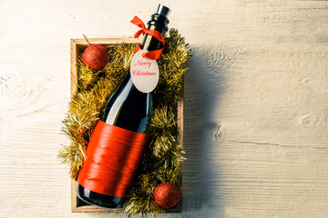 Picture of bottle of wine with card in box with tinsel
