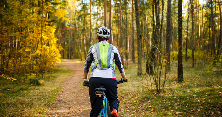 Image from back of girl in helmet on bicycle