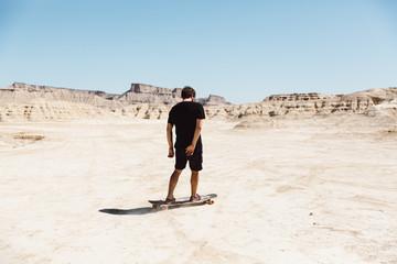 Man riding skateboard in desert