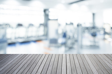 Empty top of wooden table and blurred of fitness gym background for banner presentation, healthy concept