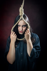 sad young woman with noose on dark red background looking at camera