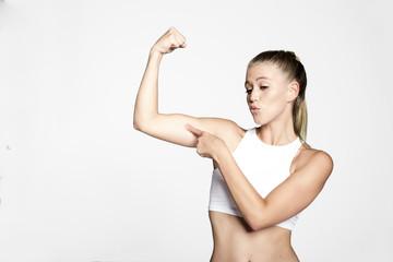junge Sportliche Frau  mit kurzem top zeigt ihre Muskeln