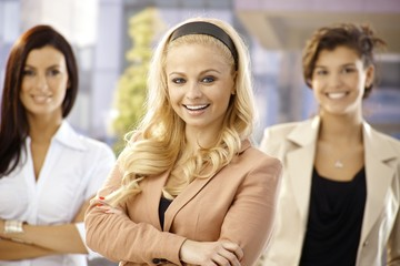 Happy businesswomen standing arms crossed