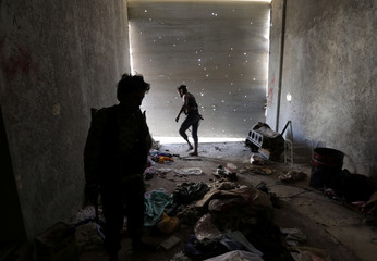 A Free Syrian Army fighter walks inside a damaged shop in the town of Tadef in Aleppo Governorate
