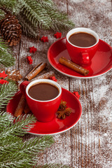 Christmas banner with green tree, cones, red cup with hot chocolate, red decoration, cinnamon on brown wooden background