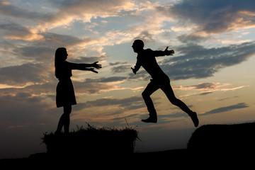 Парень и девушка в прыжке. Силуэт