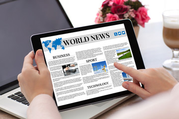 woman hands holding tablet computer  with app world news screen