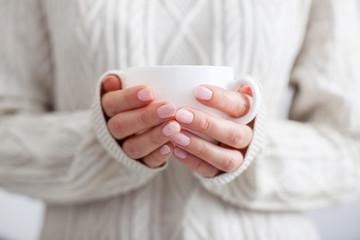 Coffee mug in female hands.