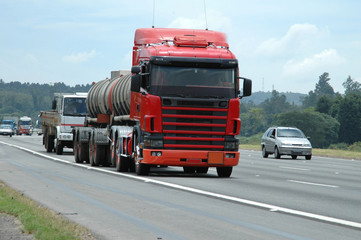 Big red no brand unmarked double tanker on the highway