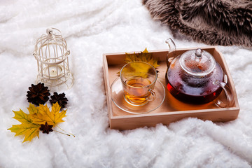 cup of tea and teapot in wooden tray on the bed. autumn home scene, Scandinavian style. A warm knitted sweater, candles and other decor