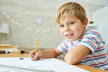Portrait of cute little boy looking at camera and smiling while sitting at desk doing homework, copy space
