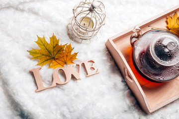 autumn home scene, Scandinavian style. A warm knitted sweater, candles, a cup of warm tea and other decor on a tray in bed. Lazy cold weekend.Love