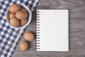 egg with open recipe book on wooden table, Top view