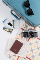 Flat lay of vintage suitcase and accessories with instant film