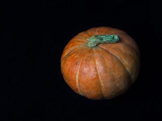 Fresh orange pumpkin isolated on black background. Top view.