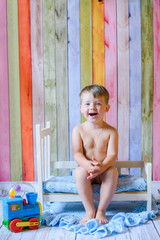 laughing kid play on wooden background on floor. Little caucasian child playing on colorful  wooden background indoor. happy Kid boy having fun at home