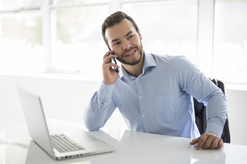 mexican attractive businessman on his 30s working at modern home office with computer laptop