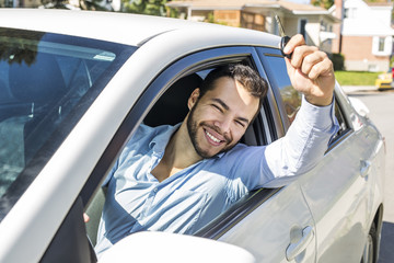 Closeup portrait, young cheerful, joyful, smiling, men holding up keys to her first new car