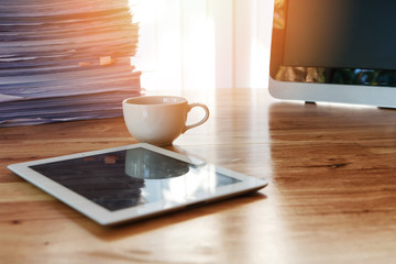 A cup of coffee with tablet and office supplies on office desk. Wooden table with office supplies in home office at morning