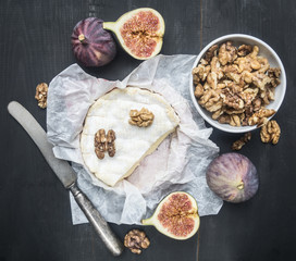 concept of appetizers for wine, camembert cheese, dark grapes, walnuts and figs with honey, on a wooden rustic background  space for text