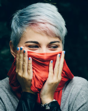 A young woman with a red scarf over her mouth.