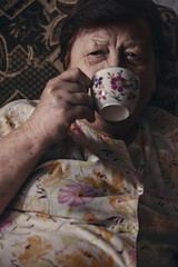 Old woman drinking tea at home