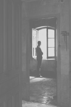 Man in Front of an Open Window in an Abandoned Room