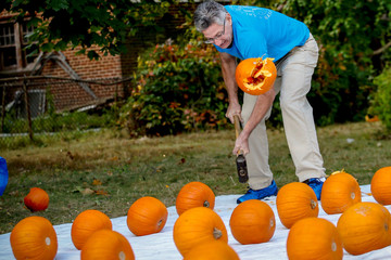 Ashrita Furman, the record holder for the most Guinness world records, smashes a pumpkin during an attempt to break the record for the most pumpkins smashed in one minute, in Queens borough of New York