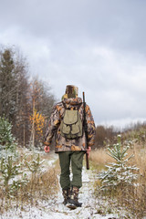 Male hunter in camouflage and with backpack, armed with a rifle, walks through the snowy winter forest.