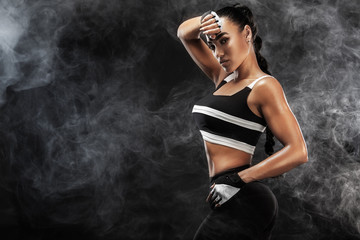 Sporty beautiful afro-american model, woman in sportwear makes fitness exercising at black background to stay fit