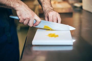 Men's hands cutting lemon zest on a cutting board