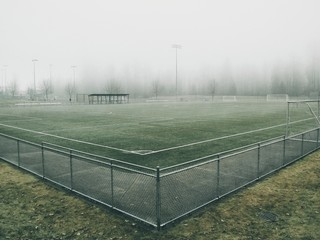 Empty soccer field on a mist covered cold day