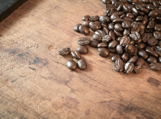 Close up dark roasted Coffee beans on wood background ( Vintage tone color ).