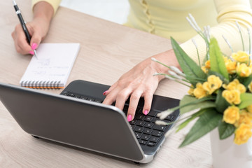 Female hands taking notes and working on laptop