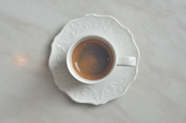 Cup Espresso (with a flower pattern on the surface) on White marble table.