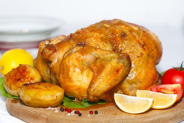 Whole roasted chicken on cutting board. Baked chicken with potatoes ready to eat.