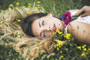 Woman laying on grass holding daisy flowers