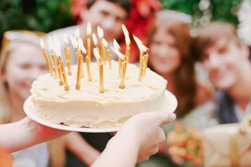 Friend giving birthday cake to birthday girl