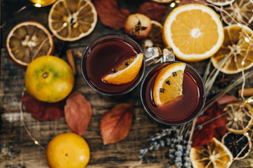 Hot mulled wine with dry orange slices, lavender and cinnamon sticks on wooden board. Space for text