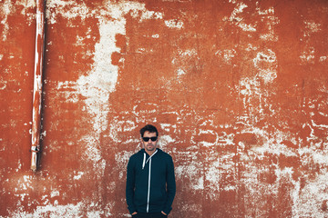 Modern young man wearing sweatshirt and sunglasses and standing in front a orange wall.