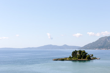 A small island sitting in a calm sea with the mainland in the background