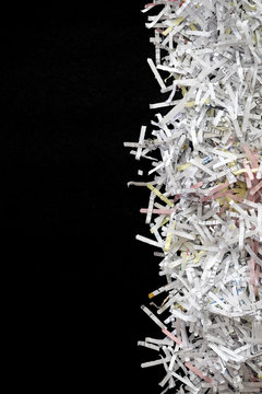 Shredded documents over black background