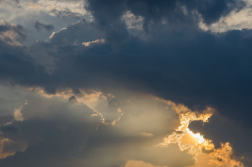 Golden sunlight beam through dark rainy cloud sky before sunset in rain season