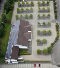 Luftaufnahme eines deutschen Supermarkts mit Solarzellen auf dem Dach und leerem Parkplatz an einem Sonntag