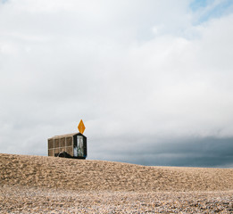 A small fisherman's hut on a pebble beach against a stormy sky