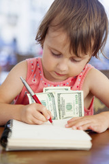 Little business child girl with US dollar banknotes plans the family budget.  Humorous picture.