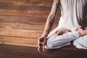 Tattooed Man Meditating in the Lotus Pose (Padmasana)