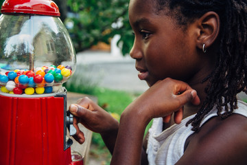 African American girl opening the lock of an old gum ball machine